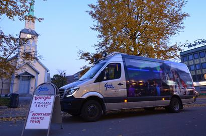 Minibus and a sales sign in front of the church. Autumn colors on the three.