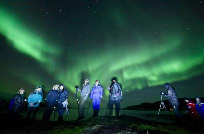 Many people with camera and tripods under the Northern Lights, by the fjord.