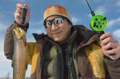 A man with a trout and ice fishing gear.