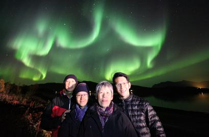 A family on four people under a star formed Northern Lights.